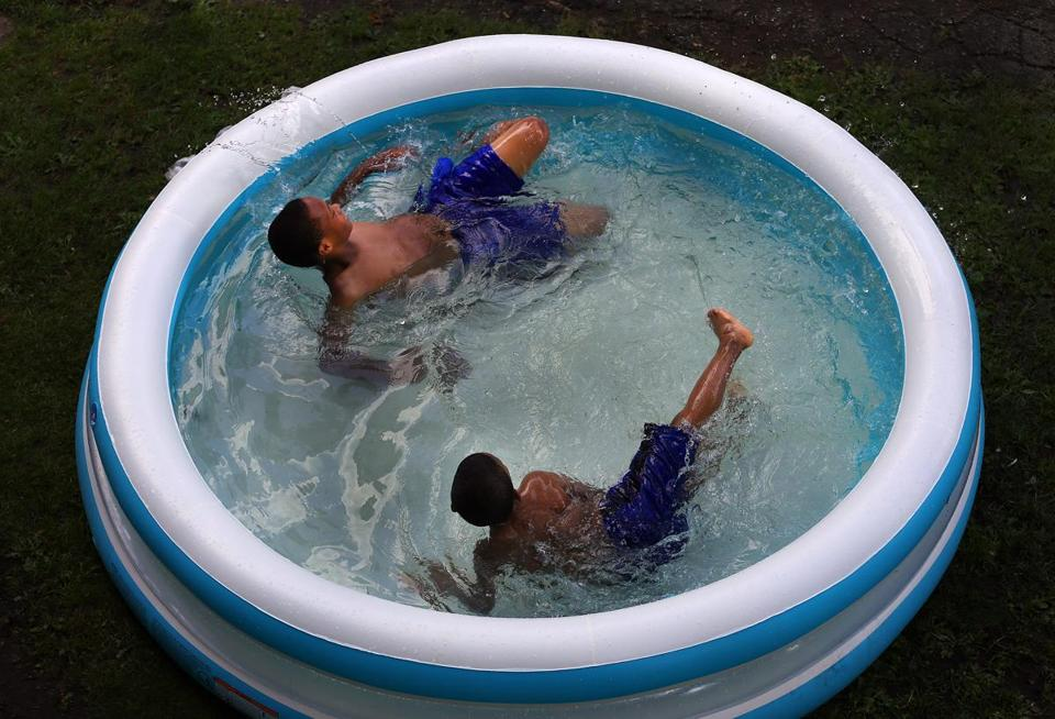 Jayewun Joslin, 9, and his friend Jaden Blass, 8, cooled off in a small pool in front of their home in South Boston.