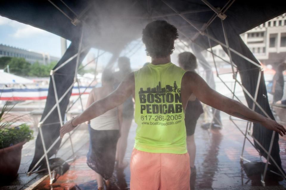 A pedicab driver cooled off at a vapor shower during a 90-degree day in Boston on Sunday.