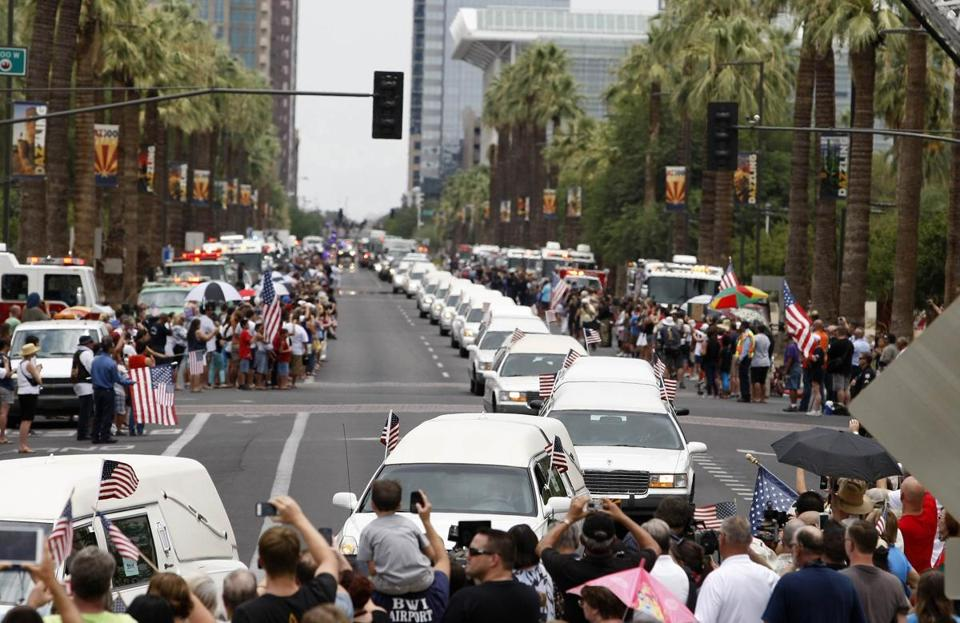 A large crowd gathered on Sunday in Phoenix as a motorcade of hearses carrying the remains of 19 members of the Granite Mountain Hotshots firefighting team left the medical examiner's office and traveled to Prescott, Ariz.
