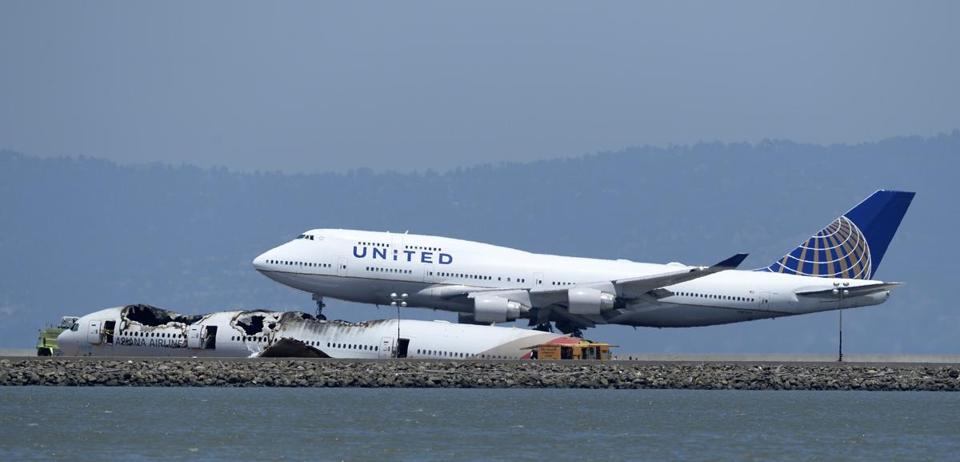 A United Airlines 747 landed Monday while passing the wreckage of the crashed Asiana plane at San Francisco International Airport.