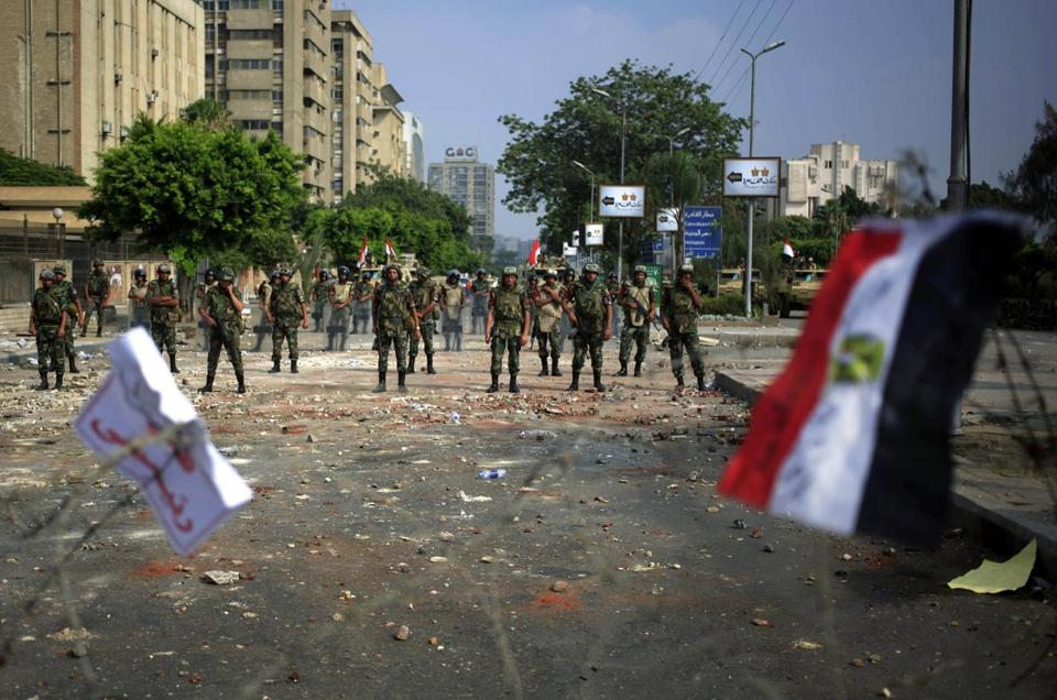 A national flag waved on the barbed wire as Egyptian soldiers stood guard at the Republican Guard building in Cairo on Tuesday.