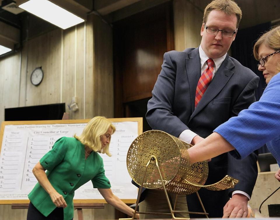 Commissioners Ellen Rooney (left) and Shawn Burke helped Geraldine Cuddyer, chairwoman of the Board of Election Commissioners, as she pulled the names from a bingo spinner.