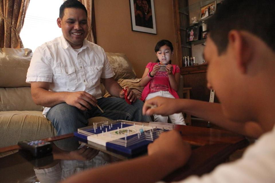 Jose Palma, with children Angela and Kevin at their home in Lynn, is part of an influx that has revitalized the city.