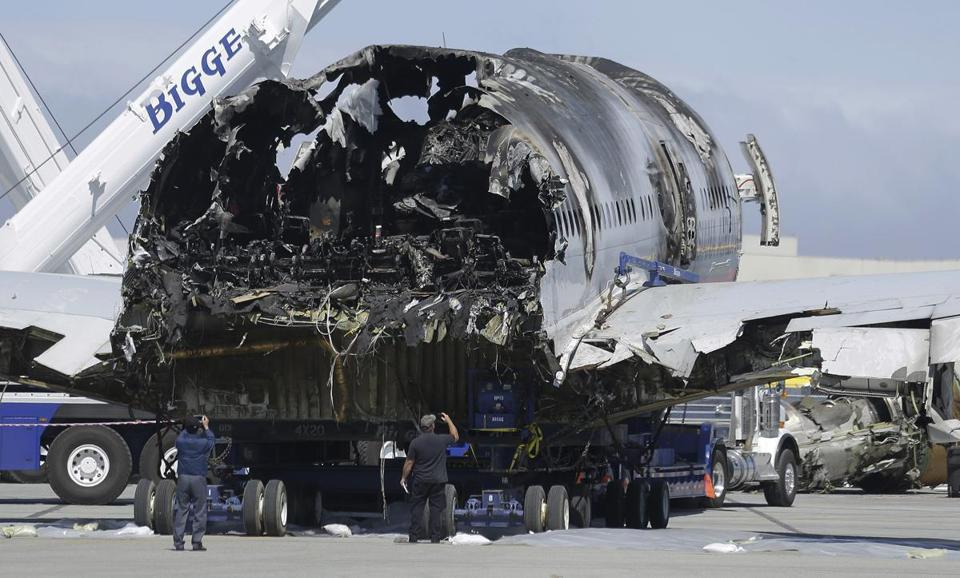 Two men took pictures of the wreckage of the Asiana Airlines jet on Friday.