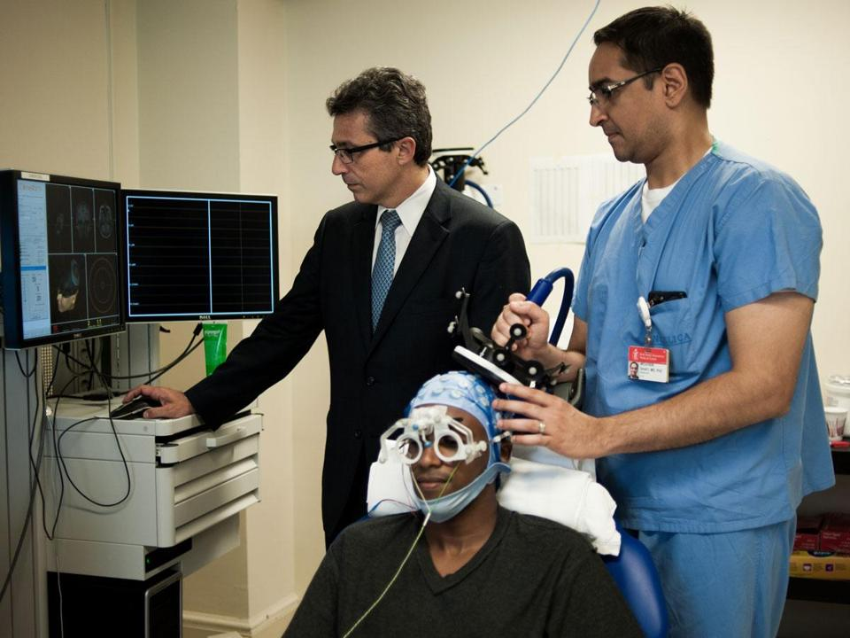 Dr. Alvaro Pascual-Leone (near right) and Dr. Mo Shafi use magnetic stimulation technology to observe brain function on a study participant at Beth Israel Deaconess Medical Center.