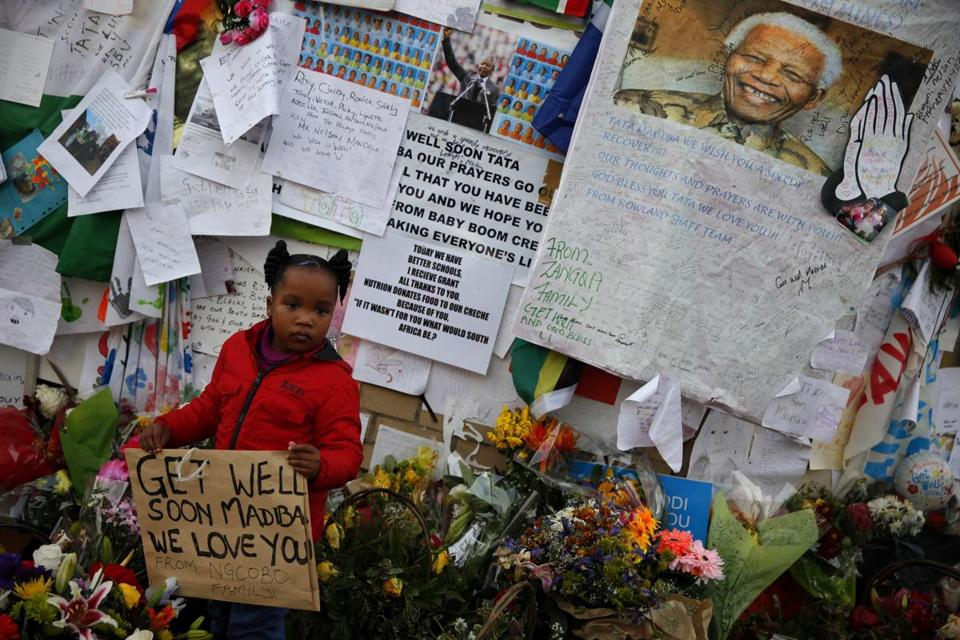 A child stood among tributes left by well-wishers outside the hospital where Nelson Mandela is being treated in Pretoria.