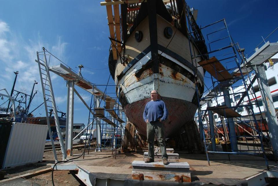 "Mayflower II skipper Peter Arenstam, standing in front of the Mayflower II at the Fairhaven Shipyard, where it is undergoing $440,000 in repairs. ""People all over Massachusetts are looking at white oak trees in yards and pastures. . . .  They really want their tree that's been growing on their yard for hundreds of years to be part of the Mayflower,"" he said.  At left, the stern of the Mayflower II."