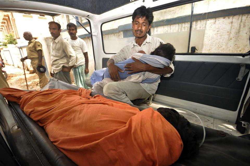 An Indian man mourned as he held his dead daughter inside an ambulance outside a hospital in Bihar, India, on Wednesday.