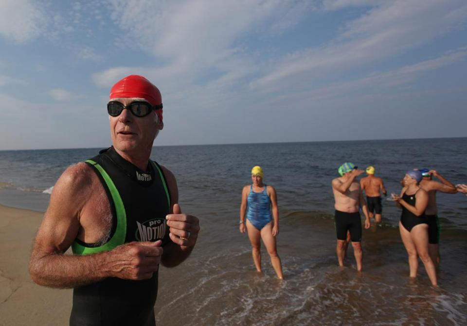 Craig Filmore (left) and others from the Newburyport group prepare for an evening swim off of Plum Island.