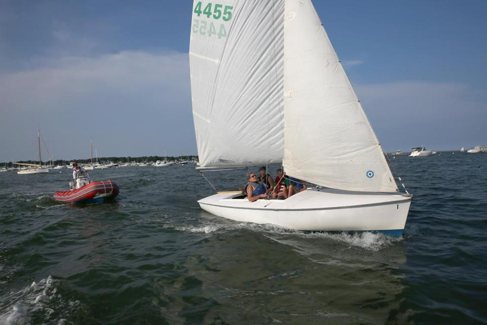 Aidan DiPrima of the Duxbury Bay Maritime School coaches Michelle Noonan and Joe Noonan, 12, in a Flying Scot last week.