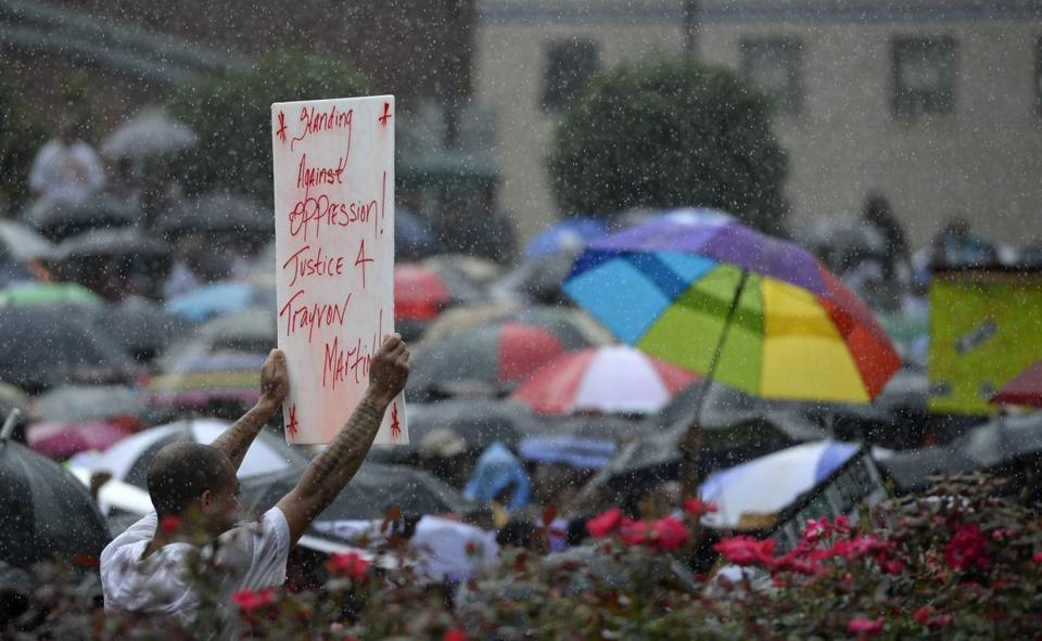 A man held up a sign in the rain during a rally in front of Atlanta's Richard B. Russell Federal Building in protest of the acquittal of George Zimmerman in the shooting death of Trayvon Martin.