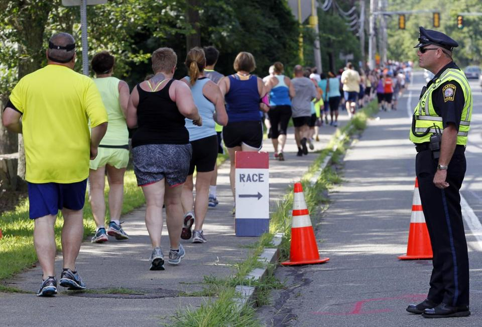 Easton Police Officer Paul Meehan watches as runners in the Narragansett Summer Running Festival pass on the sidewalk last month.