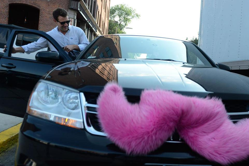 Hunter Perry gets picked up near his office on Harrison Avenue by Lyft, whose vehicles sport a pink mustache.