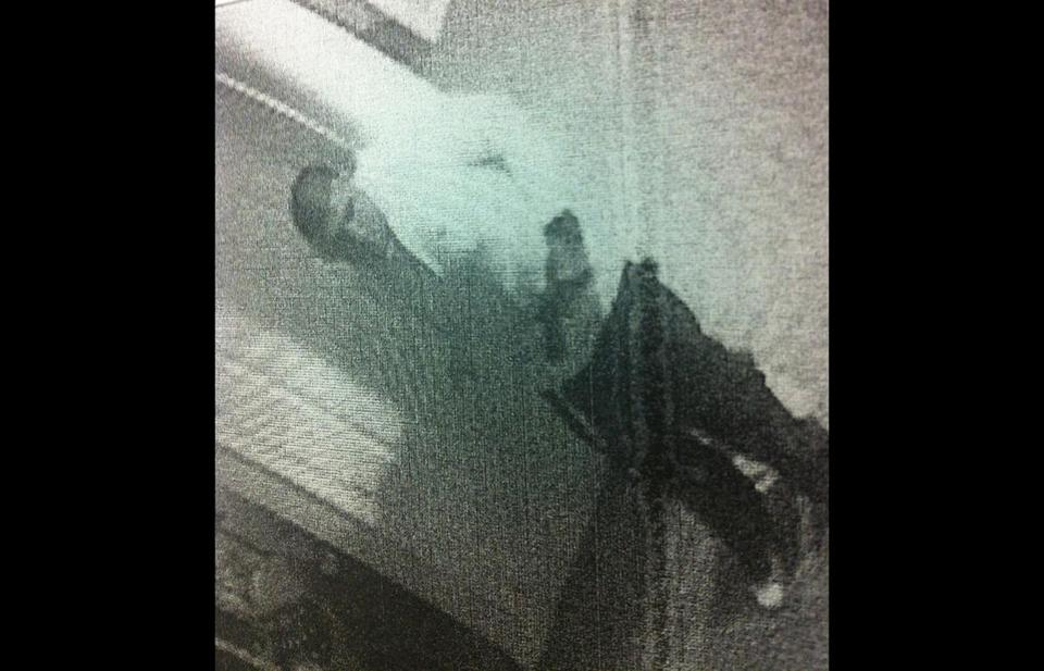Aaron Hernandez appears to be holding a pistol in this surveillance image.