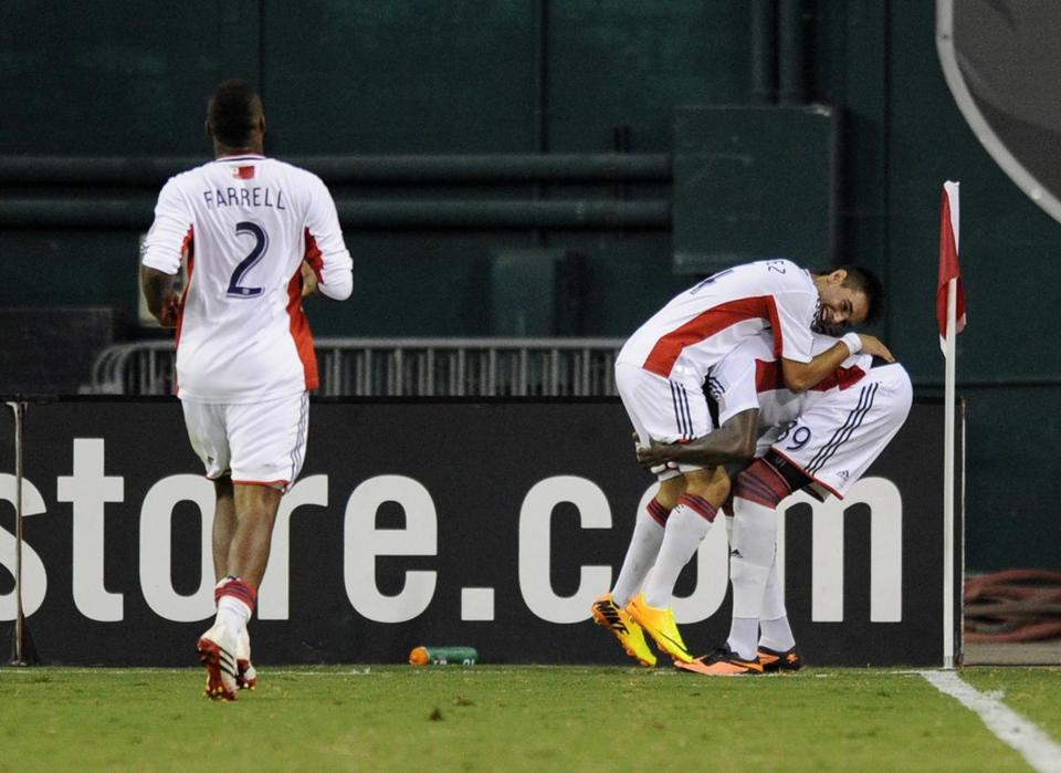 Andrew Farrell (left) is late to the party as Diego Fagundez celebrates his goal by leaping on Saer Sene.