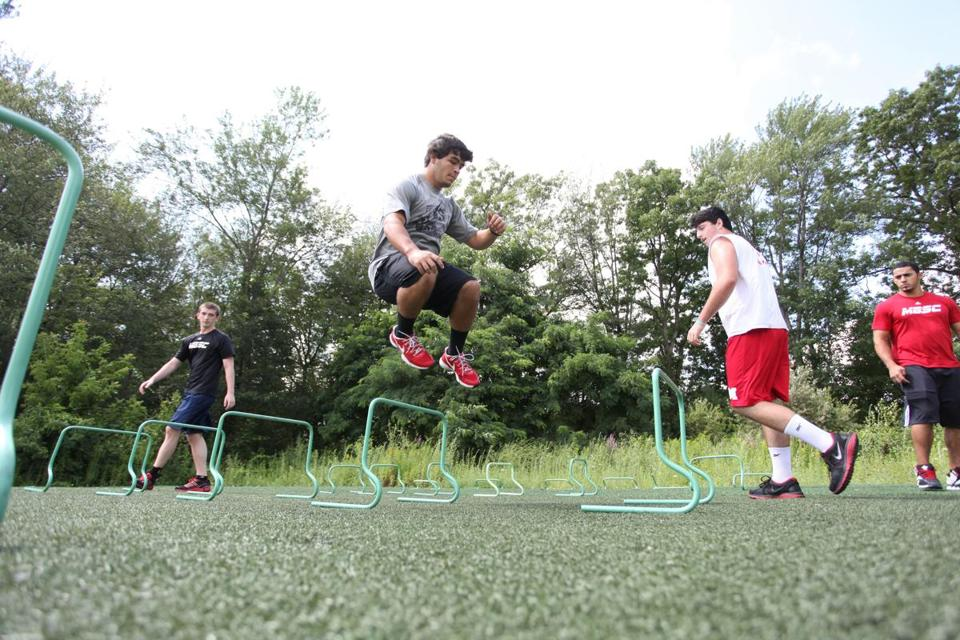 Masconomet football player Michael Tivinis jumped over hurdles during warm- ups during agility training before weight lifting at Mike Boyle's Strength and Conditioning.
