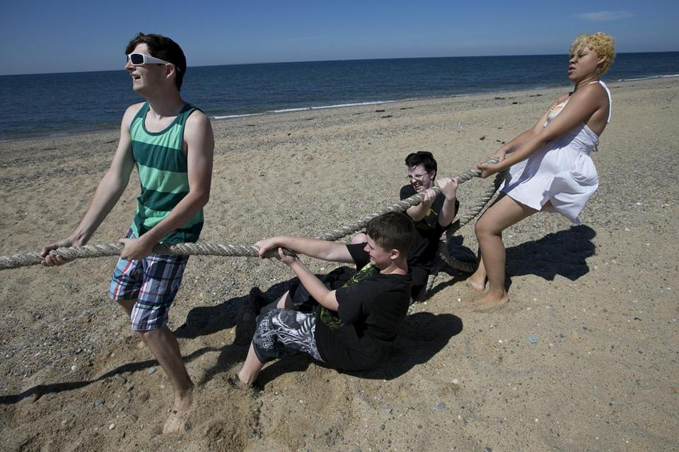 From left, Andrew Lawless, Morgan Yeager, Dan English, and Ghia Parow put their backs to a tug of war at Herring Cove Beach in Provincetown.