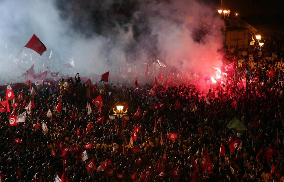 Supporters of the Islamist Ennahda party waved flags Saturday in the capital Tunis as they chant slogans in support of the government.