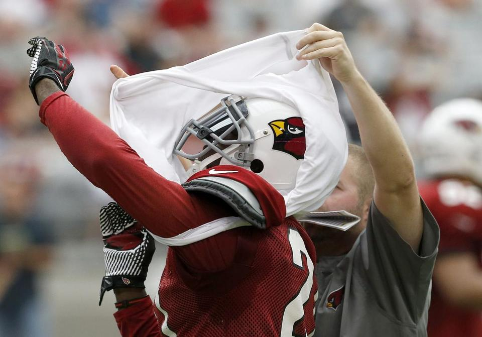 Cardinals cornerback Patrick Peterson received help taking off a white t-shirt after he played wide receiver on offense during the Cardinals' intrasquad scrimmage Saturday.