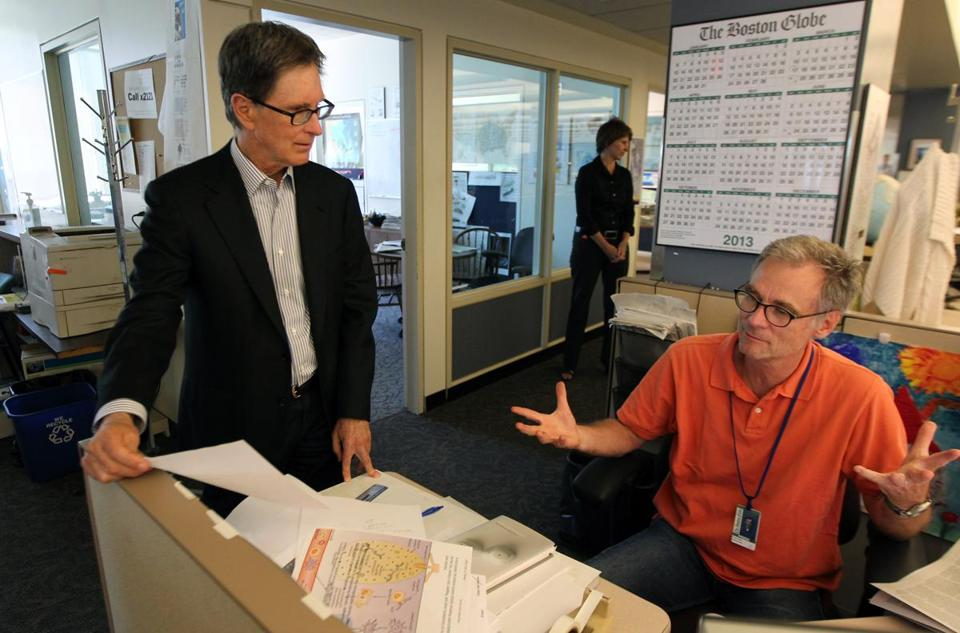 Prospective Boston Globe owner John W. Henry (left) talked with graphic designer David Butler on Monday during a newsroom tour.
