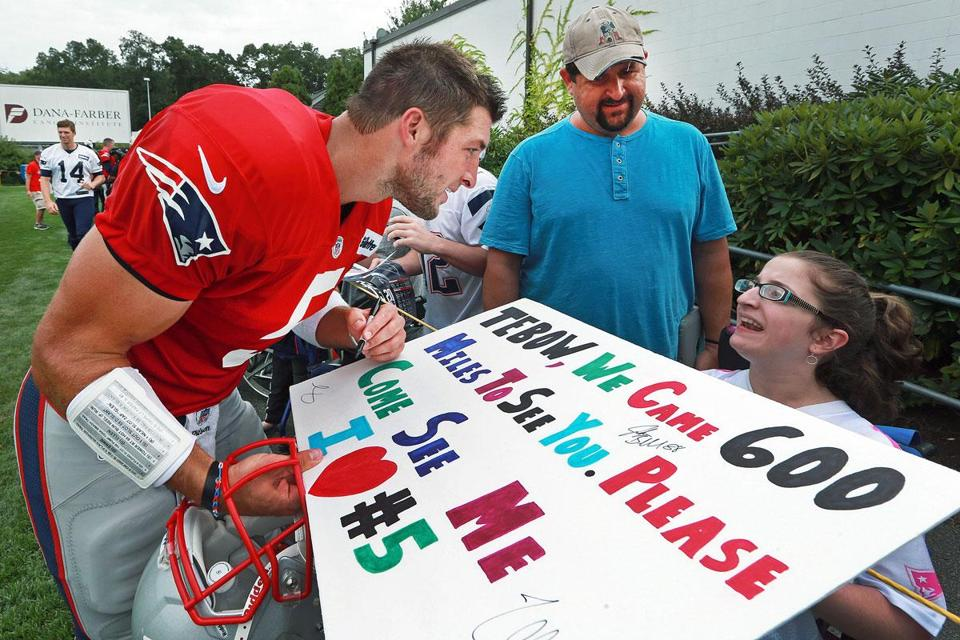 After asking her name, Tim Tebow autographs the poster of wheelchair-bound Madelin Beardsley of Virginia Beach, as her father Scott looks on.