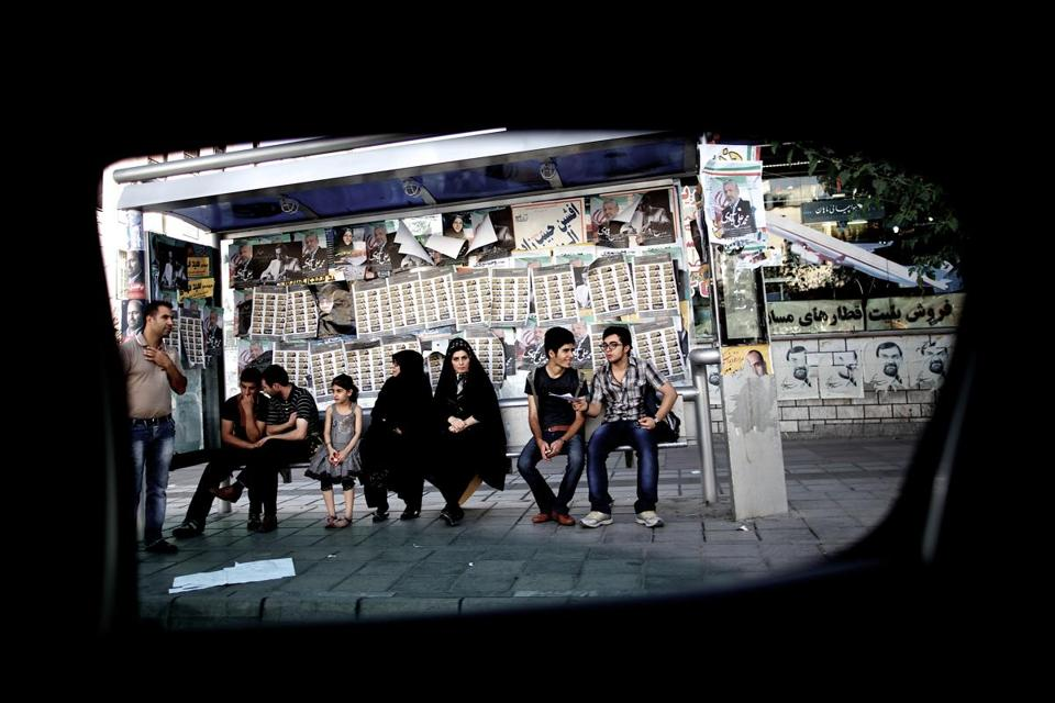 A picture taken from inside a car shows Iranians waiting at a bus station in downtown Tehran in June.