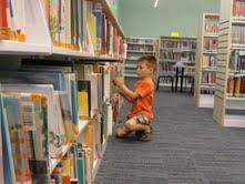 Noah McGhee browses for books in the children's room of the new Millis Public Library.