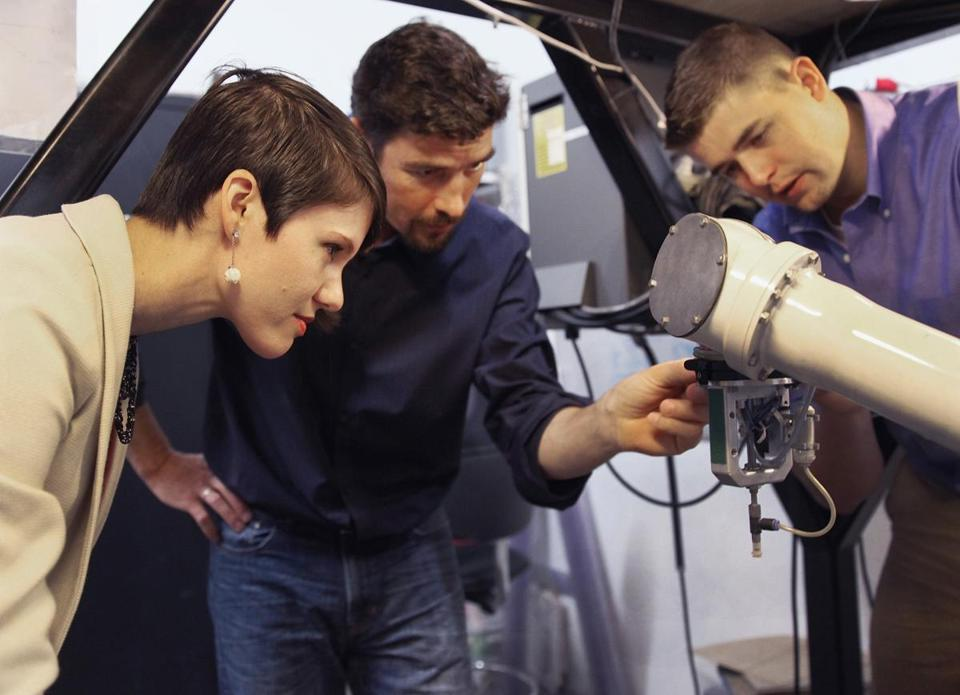 Interns Brynn Leggett (left) and Paul Heslinga (right) examined a robot with CEO Ted Acworth at Artaic, a South Boston company.