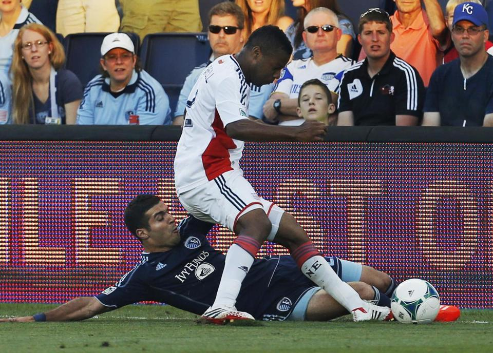 Kansas City forward Soony Saad (bottom) tries to keep the ball in bounds against Revolution defender Andrew Farrell.