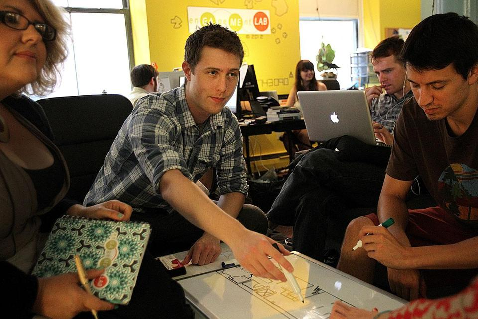 From left, Christina Wilson, Stephen Walter, and Russell Golenberg at work in the Emerson Engagement Game Lab on Boylston Street.