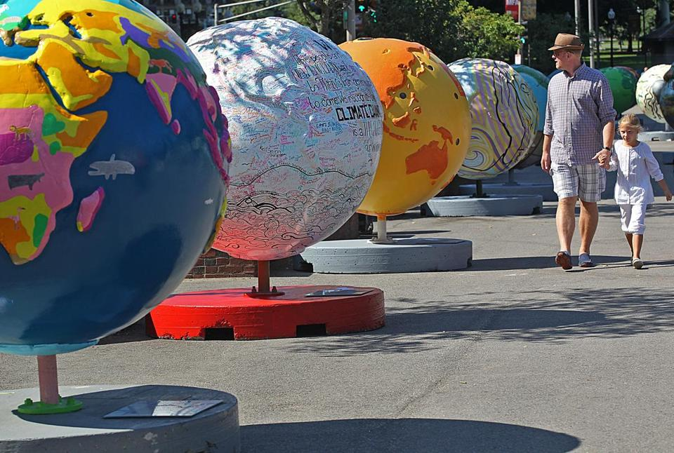"A number of globes are lined up along the Tremont Street side of the Boston Common as part of the ""Cool Globes: Hot Ideas for a Cooler Planet"" exhibit."