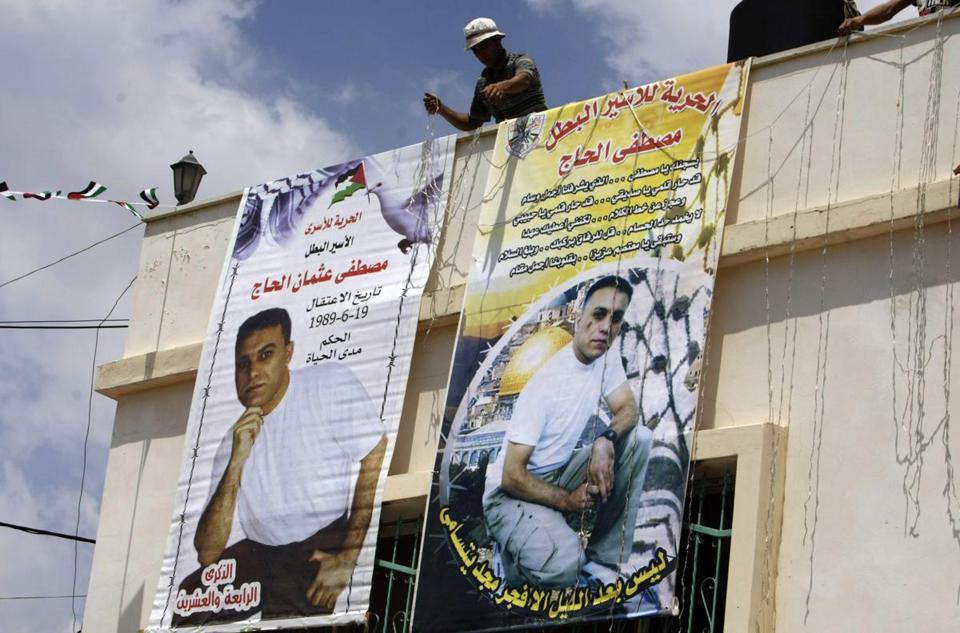 Relatives of Mustafa al-Haj put up banners in the village of Brukin, south of Nablus in the West Bank, depicting the Palestinian who killed a hiker in 1989.
