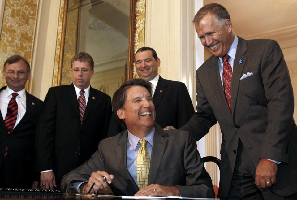 The move by Republican Governor Pat McCrory (seated) is expected to touch off a major court battle over voting rights.