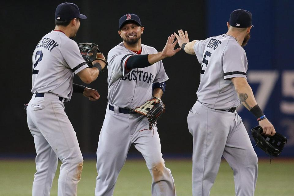 Shane Victorino (winning two-run single in the 11th) is congratulated at game's end by Jacoby Ellsbury and Jonny Gomes.