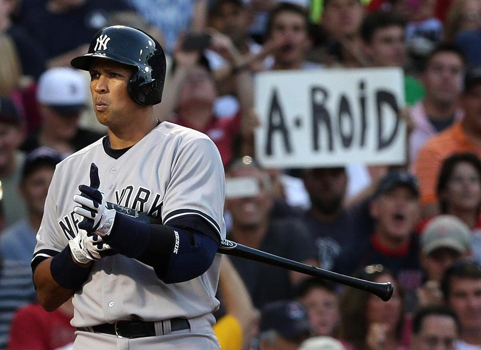 Alex Rodriguez comes to the plate for his at bat in the first inning to a chorus of boos and a signs in the stands.