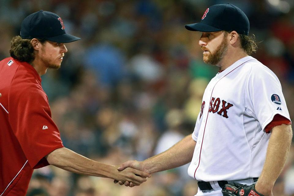 Ryan Dempster gets a handshake from teammate Clay Buchholz after exiting in the sixth, but he left the Sox in a bases-loaded jam, and they soon lost the lead.