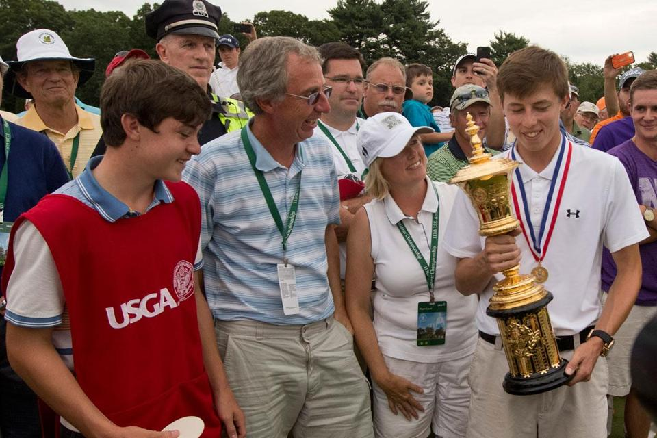 Newly crowned US Amateur champion Matt Fitzpatrick of England admires the Havemeyer Trophy along with brother/caddie Alex, father Russell, and mother Susan.