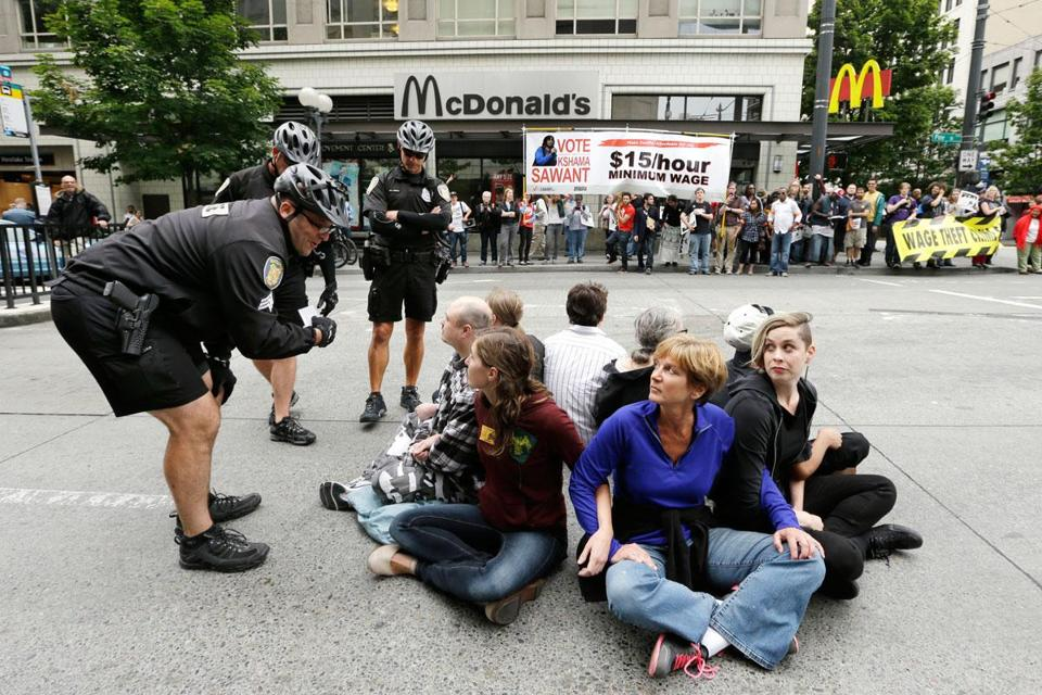 Seattle police explained the arrest procedure to protesters blocking an intersection Aug. 1. There were several arrests. Washington has the highest state minimum wage, $9.19.