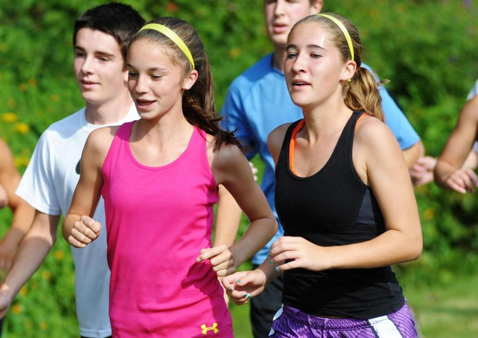 Jessica Gendreau (left) and Makenna Hunt warm up with a run  during Tyngsborough High School's varsity cross-country team practice.
