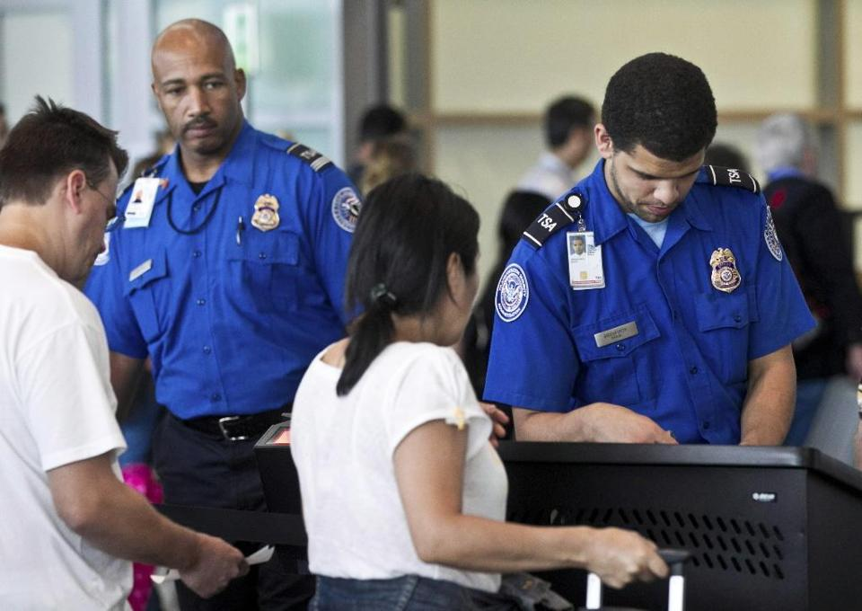 A Transportation Security Administration officer spoke with passengers and inspected their boarding passes at Logan Airport's Terminal A in August 2011.