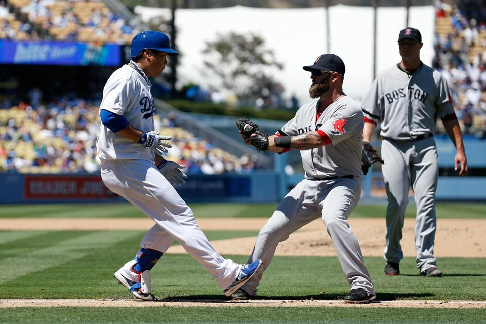 The Dodgers' Hyun-Jin Ryu is tagged out by first baseman Mike Napoli on a sacrifice bunt.