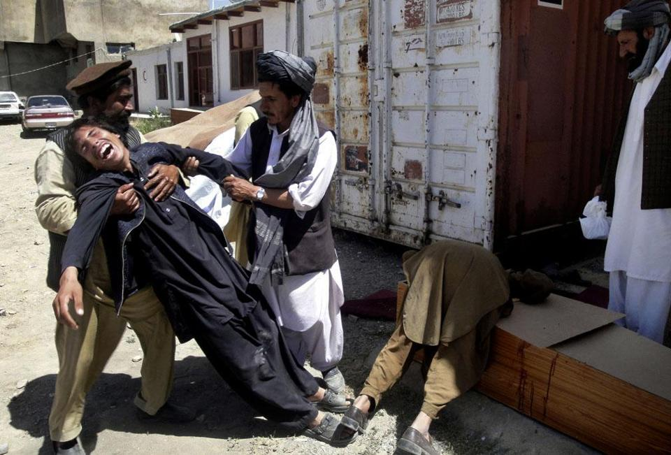 Afghans helped a man on Tuesday after more violence south of Kabul. Insurgents are trying to regain territory.
