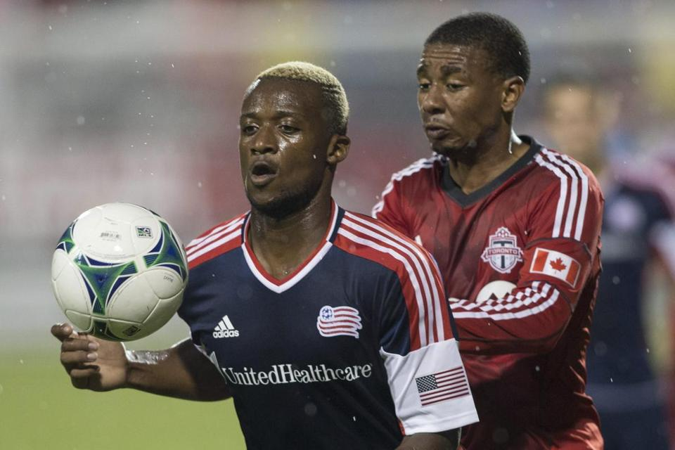 Revolution striker Dimitry Imbongo shielded the ball from Toronto FC's Reggie Lambe during the second half Friday.