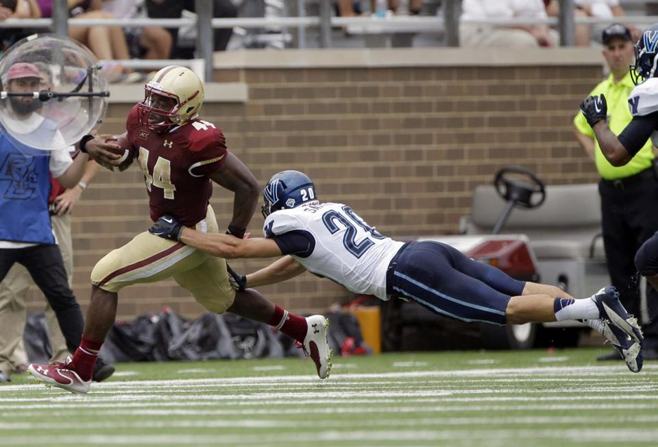 Boston College running back Andre Williams (left) rushed down the sideline as Villanova defensive back Joe Sarnese dove in for the tackle.