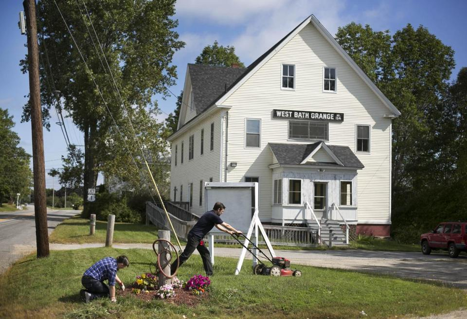 Angela and John Brigance spruced up the landscaping at the 110-year-old Grange building in West Bath, Maine, at the start of the weekend.