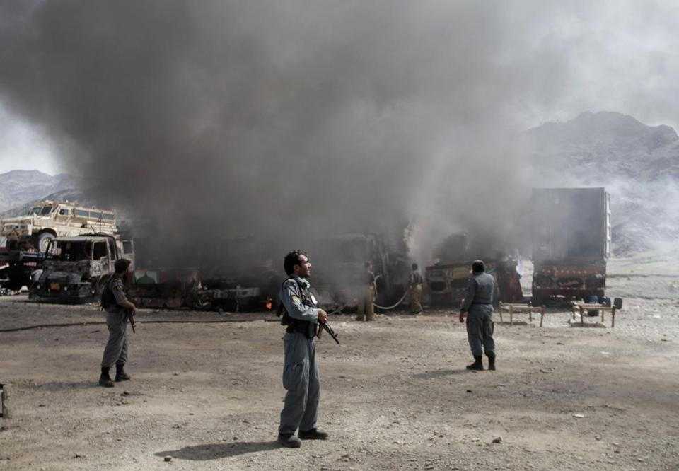 Afghan police officers watched the site of a militant attack near the Pakistan-Afghanistan border as NATO supply trucks burned.