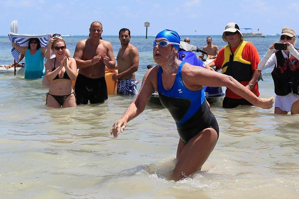 American Diana Nyad walked to dry sand Monday after becoming the first person to swim from Cuba to Key West, Fla., without a shark cage.