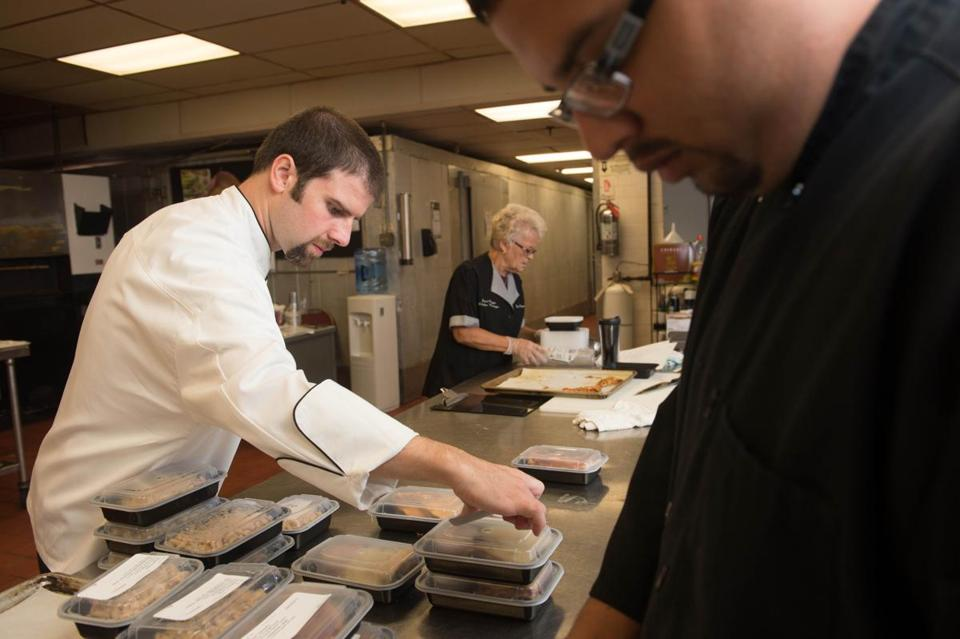 At Lantana in Randolph, culinary director Steven Kammann, Janet Baggs, and Javier Ramirez pack Smart Lunches meals.