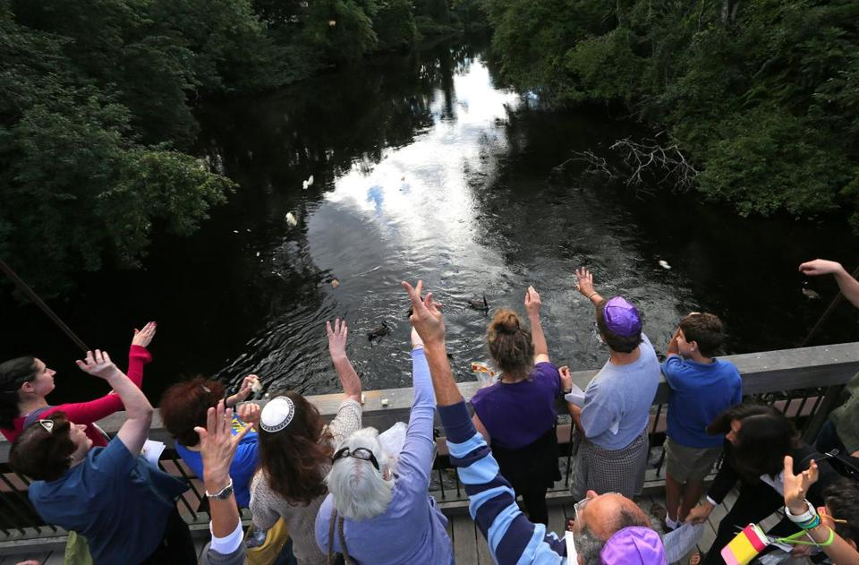 Members of the Shir Hadash congregation took part in a Tashlich service on Rosh Hashanah, symbolically casting away sins by throwing bread into moving water, at the pedestrian bridge over the Charles River at Albemarle Street in Newton.