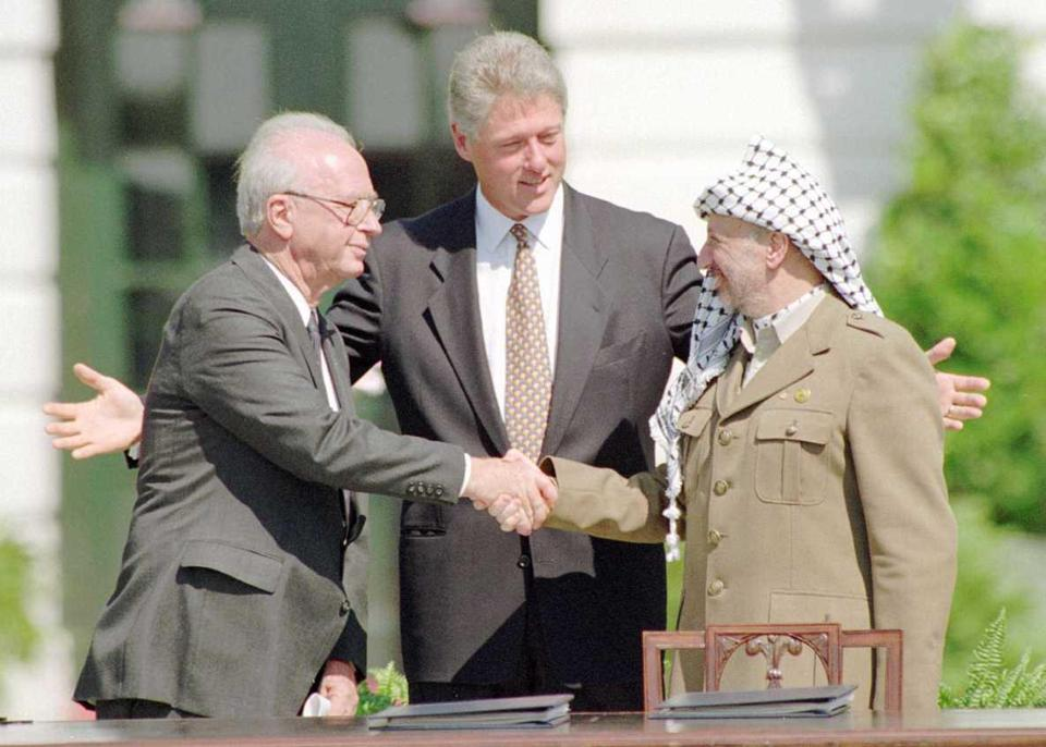 President Bill Clinton coaxes Israeli Prime Minister Yitzhak Rabin, left, and PLO Chairman Yasser Arafat to shake hands at the White House Sept. 13, 1993, at the signing of their peace accord.